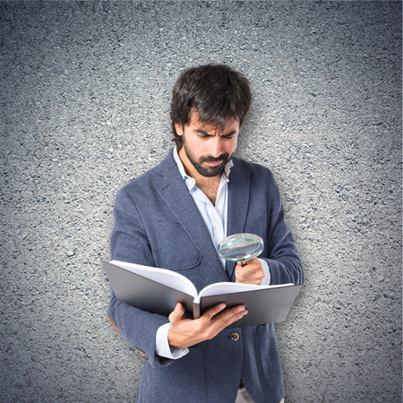 Businessman with loupe reding a book over textured background photo