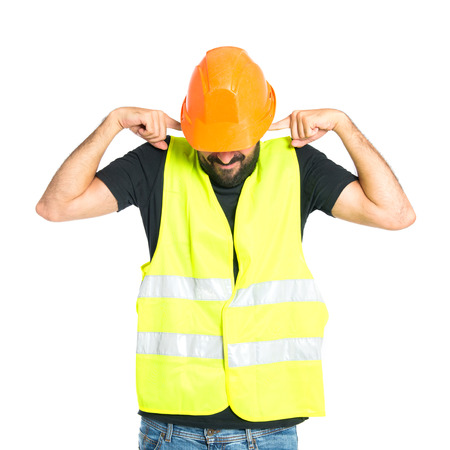 Workman covering his ears over white background photo