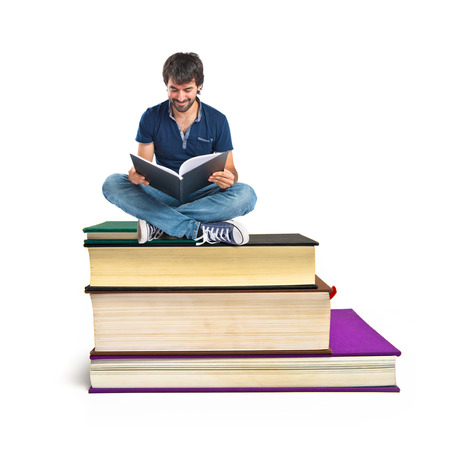 Man reading a book sitting on books photo