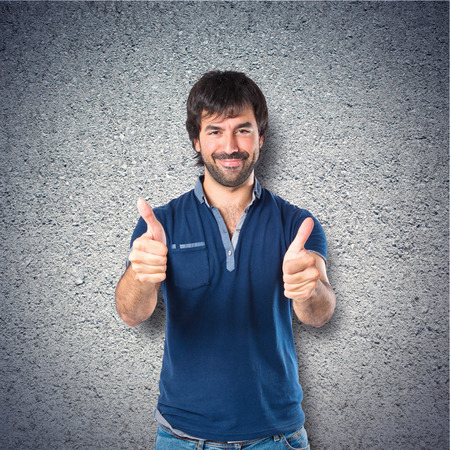 Man with thumb up over textured background photo