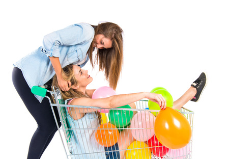 playing the market: Friends playing with balloons and supermarket cart Stock Photo