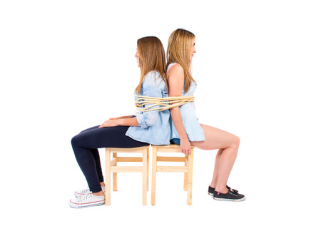Sisters kidnapped and tied to a chair Stock Photo