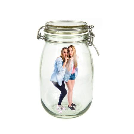 Friends making silence gesture inside jar glass photo