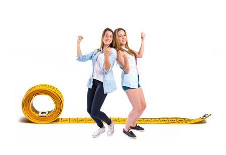 Lucky girls around tape measure over white background photo