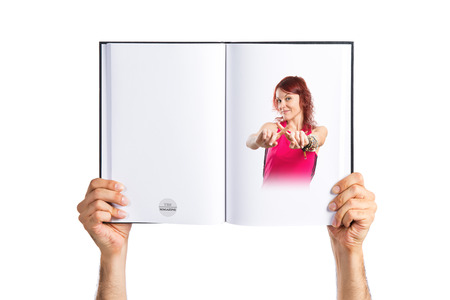 Young girl crossing her fingers printed on book photo