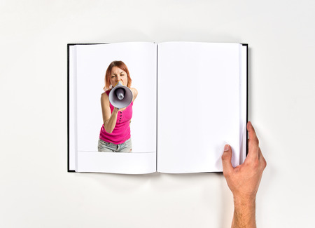 Redhead girl shouting with a megaphone printed on book photo