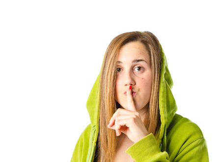 girl making silence gesture over isolated white background photo