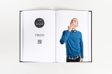 Redhead man yawning printed on book