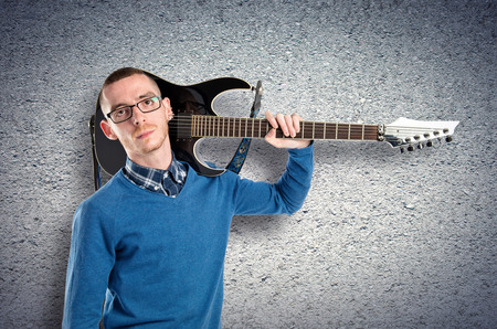 Young man with his guitar over textured background photo