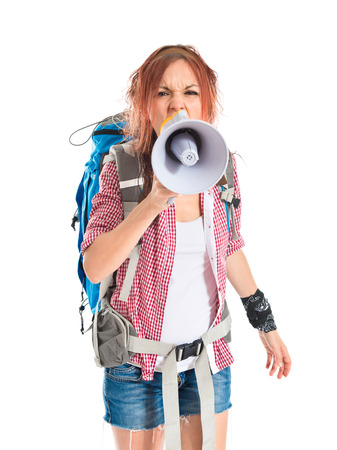 backpacker shouting by megaphone over white background photo