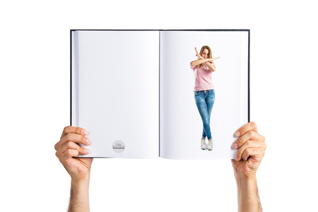 Girl making stop sign printed on book photo