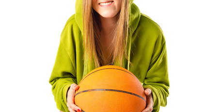 Blonde girl playing basketball over white background photo