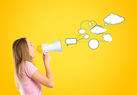 Blonde girl shouting with a megaphone over yellow background photo