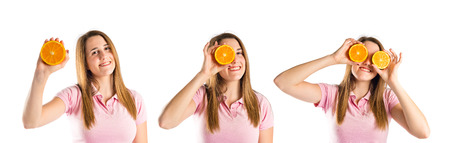 Young girl playing with oranges over white background photo