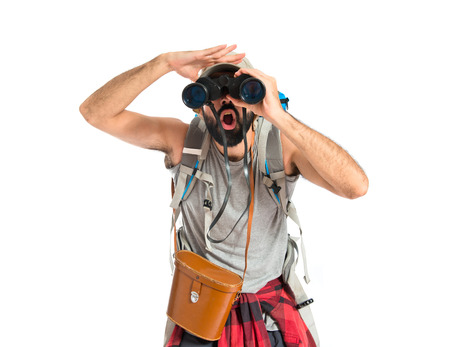 Backpacker with binoculars over isolated white background photo