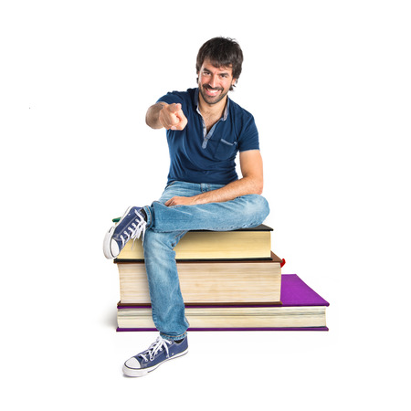 Man pointing to the front sitting on book photo