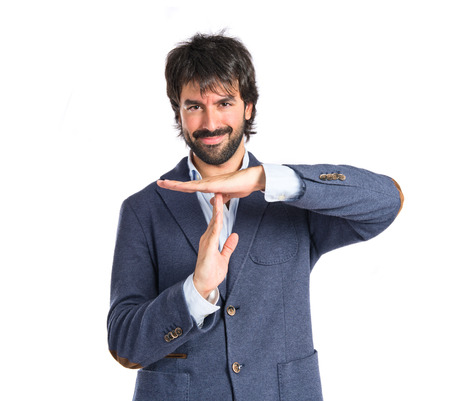 hand stop: Happy man making time out gesture over white background