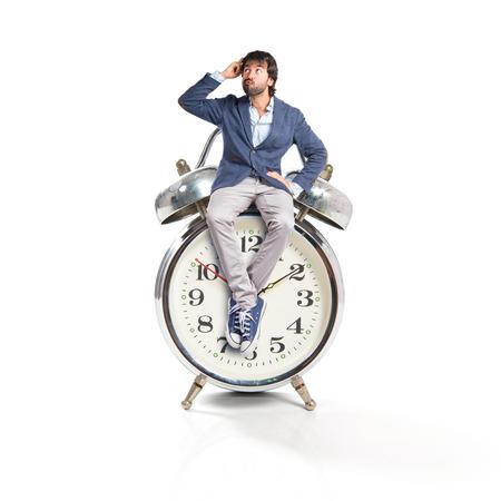 Man thinking and sitting on vintage clock photo