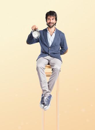 Man holding a clock over ocher background photo