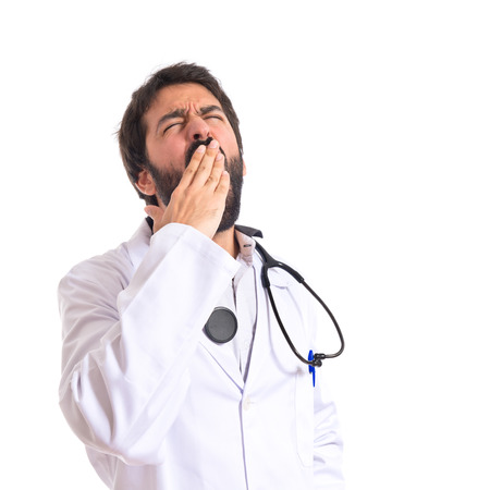 Doctor yawning over isolated white background photo