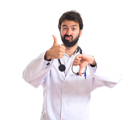 Doctor making a good-bad sign over white background photo