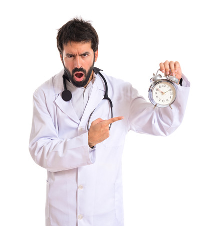 Surprised doctor holding a clock over white background photo