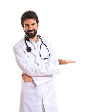 Doctor presenting something over isolated white background photo
