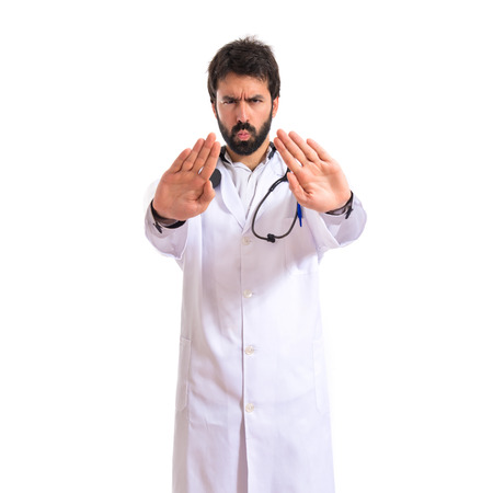 Doctor making stop sign over white background photo