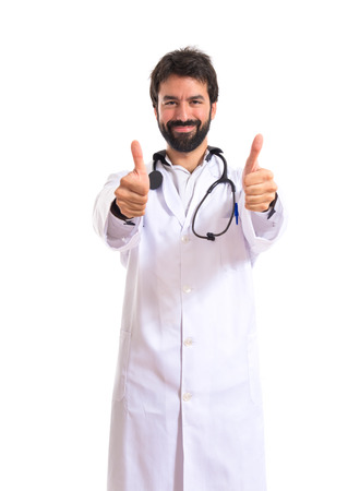 Doctor with thumbs up over white background photo