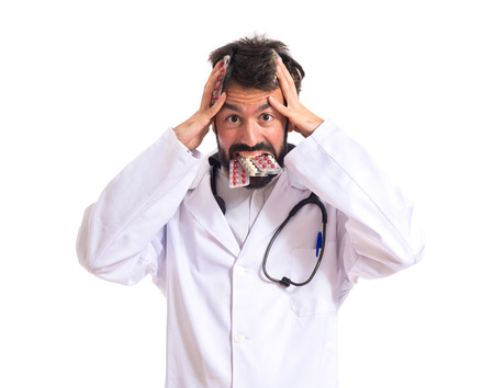Frustrated doctor with pills over white background photo