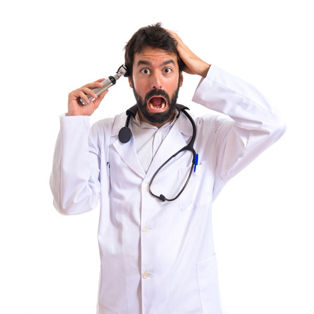 otorhinolaryngologist: Crazy otorhinolaryngologist with his otoscope over white background Stock Photo