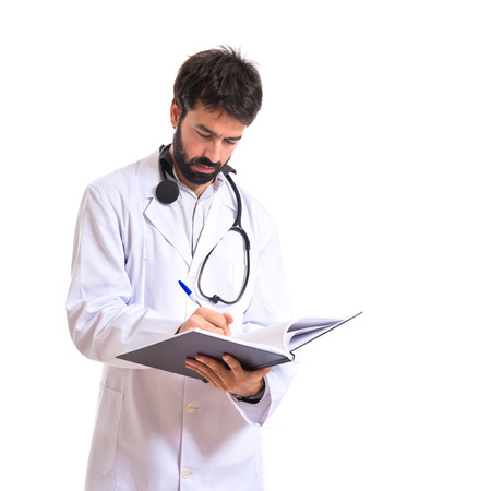 Doctor reading a book over white background photo