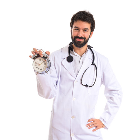 Doctor holding a clock over white background photo