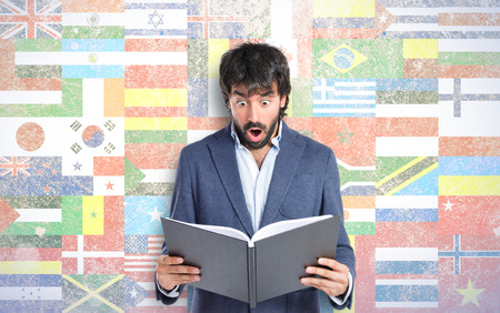 Surprised man reading a book over flags background photo