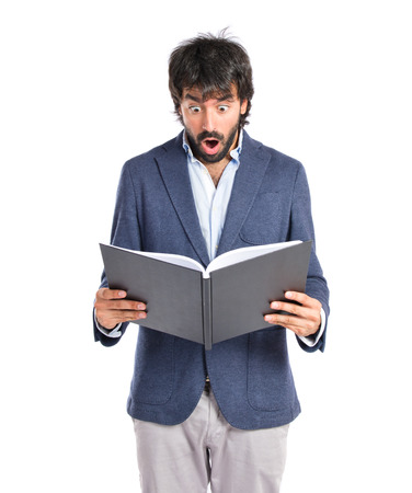 Surprised man reading a book over white background photo