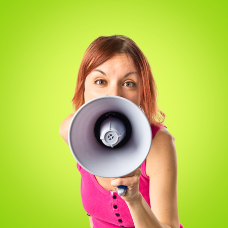 Redhead girl shouting with a megaphone over green background photo