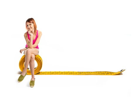 Redhead girl sitting on tape measure