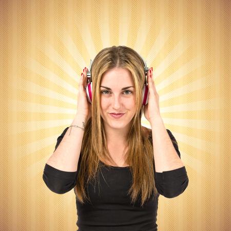 Young blonde girl listening music over pop background photo