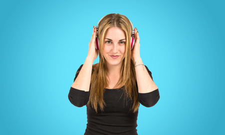 Young blonde girl listening music over blue background photo