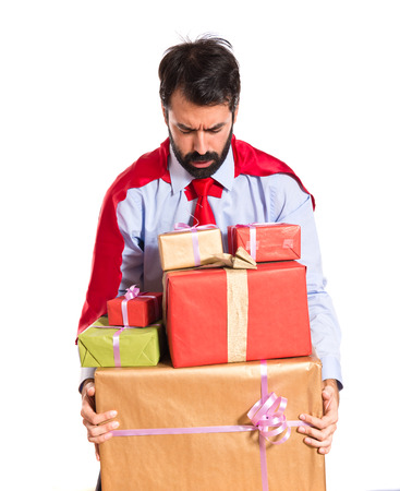 Businessman dressed like superhero holding gifts photo