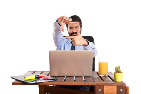 Businessman in his office focusing with his fingers Stock Photo