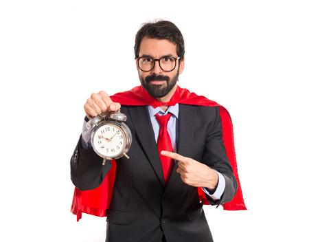 Businessman dressed like superhero holding a clock photo