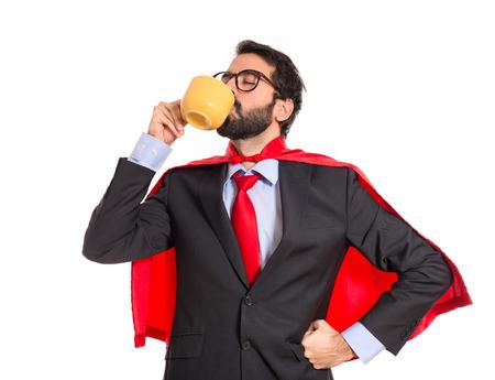 Businessman dressed like superhero drinking coffee photo