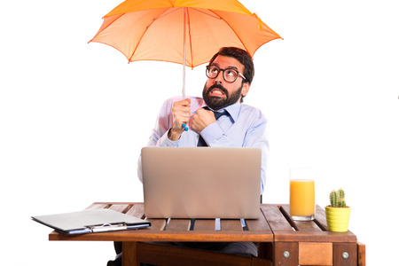 Businessman in his office holding an umbrella photo