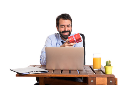 Businessman in his office giving a gift photo