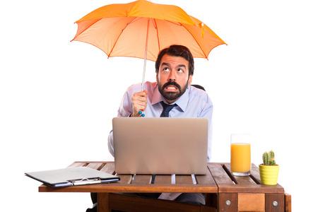 lluvia paraguas: Hombre de negocios en su oficina que sostiene un paraguas