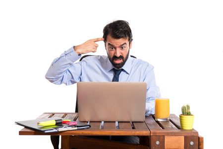 Businessman in his office making crazy gesture photo