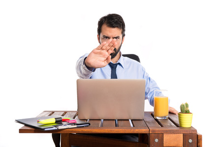 violence in the workplace: Businessman in his office making stop sign Stock Photo