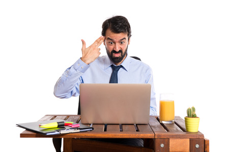 Businessman in his office making suicide gesture photo
