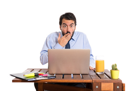 Businessman in his office doing surprise gesture photo